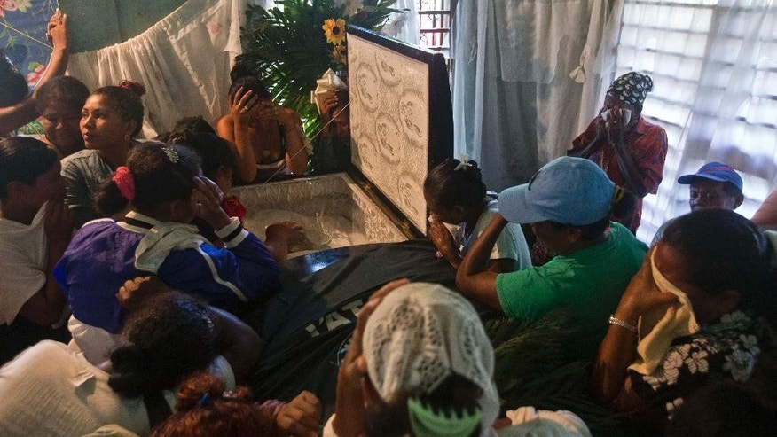 Relatives of Mario Leman, leader of the Miskito political party YATAMA, mourn during Leman's wake in the Caribbean coastal town Waspam, Nicaragua, Thursday, Sept. 17, 2015. Leman was killed during a recent clash between a group of Sandinistas and YATAMA members. The Miskito people claim that tensions began when they began expelling squatters who had occupied parts of their land. (AP Photo/Esteban Felix)