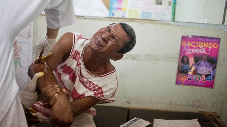 Rosman Flores, a member of the Miskito people Council of Elders, winces in pain as a doctor cleans a bullet wound he received a day earlier, in Waspam, Nicaragua, Thursday, Sept. 17, 2015. Flores says he was injured when shot at by Nicaraguan Army soldiers while he and two others were making food runs to surrounding Miskito communities. According to officials, Flores was shot by Nicaraguan Armed Forces for failure to stop at a checkpoint. (AP Photo/Esteban Felix)