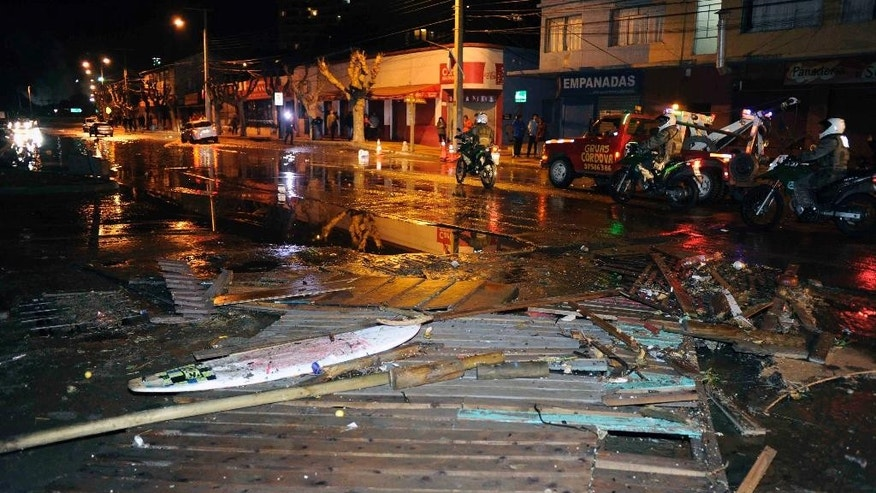 A car is surrounded by debris in a flooded street after an earthquake-triggered tsunami hit Concon, Chile, Thursday, Sept. 17, 2015. Several coastal towns were flooded from small tsunami waves set off by late Wednesday's magnitude-8.3 earthquake, which shook the Earth so strongly that rumbles were felt across South America. (AP Photo/Matias Delacroix) CHILE OUT - NO USAR EN CHILE