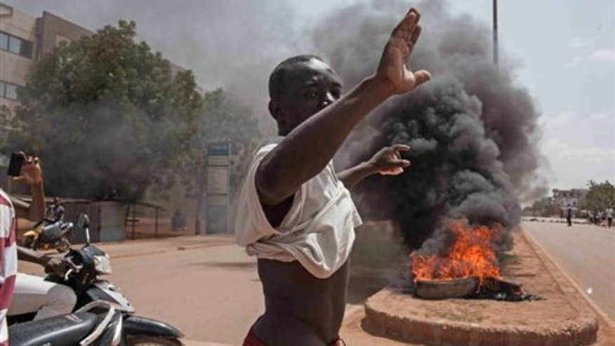 Sept. 17, 2015: A Burkina Faso protester gestures in front of burning tires as he and others take to the streets in the city of Ouagadougou, Burkina Faso.