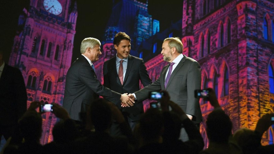 New Democratic Party leader Tom Mulcair, right, shakes hands with Conservative Prime Minster Stephen Harper, left, as Liberal leader Justin Trudeau, center, looks on during their introduction prior to a debate, Thursday, Sept. 17, 2015 in Calgary, Alberta. (Sean Kilpatrick/The Canadian Press via AP) MANDATORY CREDIT