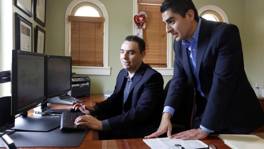 In this Friday, Aug. 21, 2015 photo, certified financial planners Aaron Munoz, left, and Gilbert Cerda, pose for a photo at their offices in Downey, Calif. Their company, Cerda Munoz Advisors, offers financial advice with a focus on the Hispanic population.  (AP Photo/Damian Dovarganes)