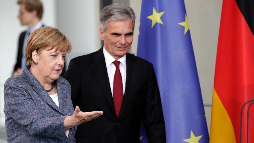 German Chancellor Angela Merkel, left, and Austrian Chancellor Werner Faymann, right, arrive for a joint press conference after a meeting at the chancellery in Berlin, Germany, Tuesday, Sept. 15, 2015. Merkel said her country and Austria are calling for a special European Union summit next week to discuss the continent's migration crisis. (AP Photo/Michael Sohn)