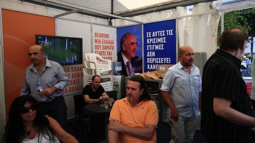 Supporters of the conservative New Democracy party,  backdropped by a picture of their leader Vangelis Meimarakis, sit at the party's main election kiosk in central Athens, Wednesday, Sept. 16, 2015. The banners read in Greek: ' We want Greece to produce , export and prosper', left, and 'In these critical times, noone is spared', right. Greece is holding a snap general election on Sept. 20, 2015. It is the third time this year Greeks will be voting, with the economy still in dire straits, a quarter of workers jobless, and capital controls limiting cash access to savings to 420 euros ($470) per week. (AP Photo/Lefteris Pitarakis)
