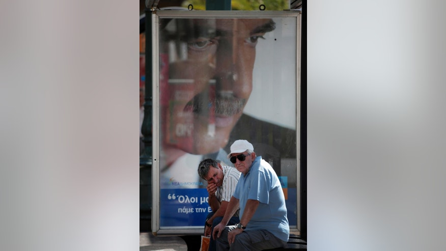 Commuters wait at a bus stop decorated with a poster of Vangelis Meimarakis, the leader of conservative New Democracy party, in central Athens, Wednesday, Sept. 16, 2015. Greece is holding a snap general election on Sept. 20, 2015. It is the third time this year Greeks will be voting, with the economy still in dire straits, a quarter of workers jobless, and capital controls limiting cash access to savings to 420 euros ($470) per week. (AP Photo/Lefteris Pitarakis)