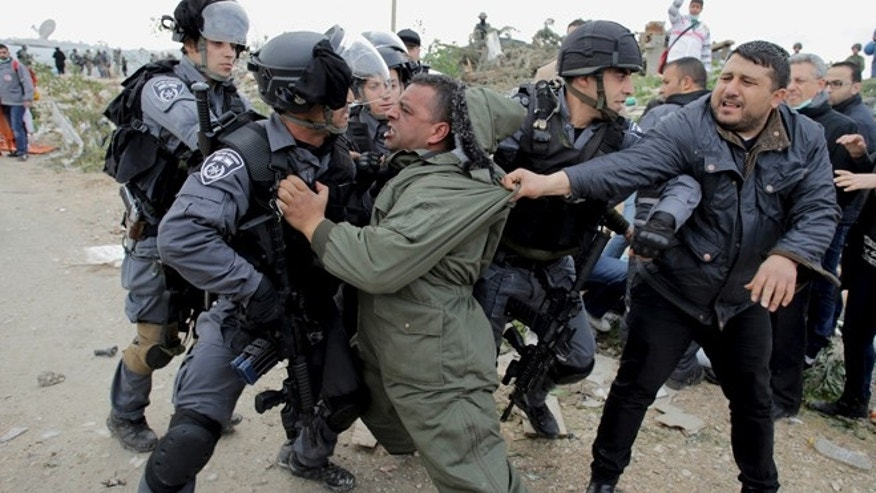 Feb. 16, 2015: A Palestinian man scuffles with Israeli border policemen as they clear a protest on land that Palestinians said was confiscated by Israel for Jewish settlements.