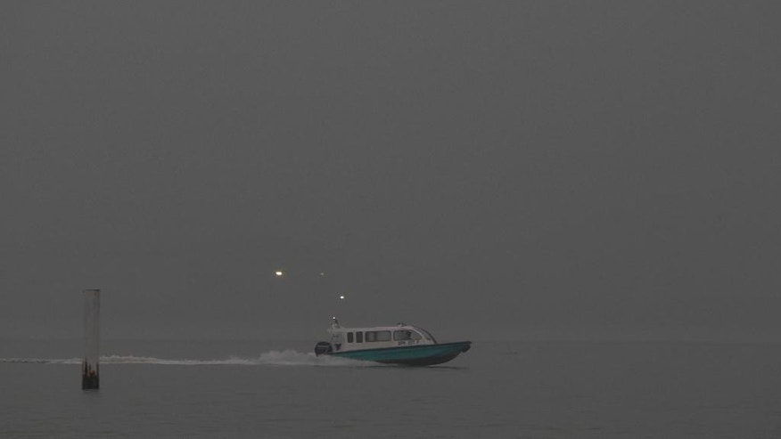 A speed boat cruises fast in Port Klang shrouded with haze in Klang, outside Kuala Lumpur, Malaysia Thursday, Sept. 17, 2015. Wildfires caused by illegal land clearing in Indonesia's Sumatra and Borneo islands often spread choking haze to neighboring countries such as Malaysia and Singapore. (AP Photo/Joshua Paul)