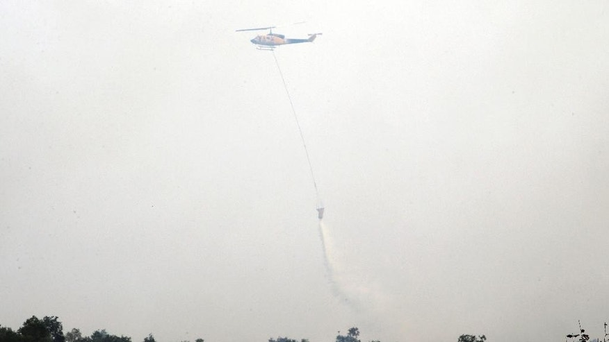A helicopter drops water to extinguish forest fire in Ogan Ilir, South Sumatra, Indonesia, Thursday, Sept. 17, 2015. Indonesia intensifies efforts to extinguish the forest fires that cause the haze, which blanketed parts of the archipelago and neighboring countries. (AP Photo/Tatan Syuflana)