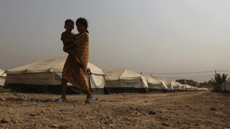 Afaf Mahmoud, an 11-year-old internally displaced Iraqi, carries her brother at a camp in Baghdad's western neighborhood of Ghazaliyah, Iraq, Wednesday, Sept. 16, 2015. The camp accommodating people from Anbar province's Ramadi and around received humanitarian aid Wednesday. (AP Photo/Hadi Mizban)