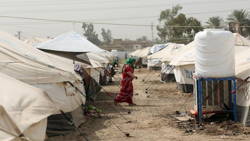 An internally displaced Iraqi walks between rows of tents at a refugee camp in Baghdad's western neighborhood of Ghazaliyah, Iraq, Wednesday, Sept. 16, 2015. The camp accommodating people from Anbar province's Ramadi and around received humanitarian aid Wednesday. (AP Photo/Hadi Mizban)