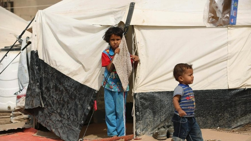 Iraqi children internally displaced stand outside their tent at a refugee camp in Baghdad's western neighborhood of Ghazaliyah, Iraq, Wednesday, Sept. 16, 2015. The camp accommodating people from Anbar province's Ramadi and around received humanitarian aid Wednesday. (AP Photo/Hadi Mizban)