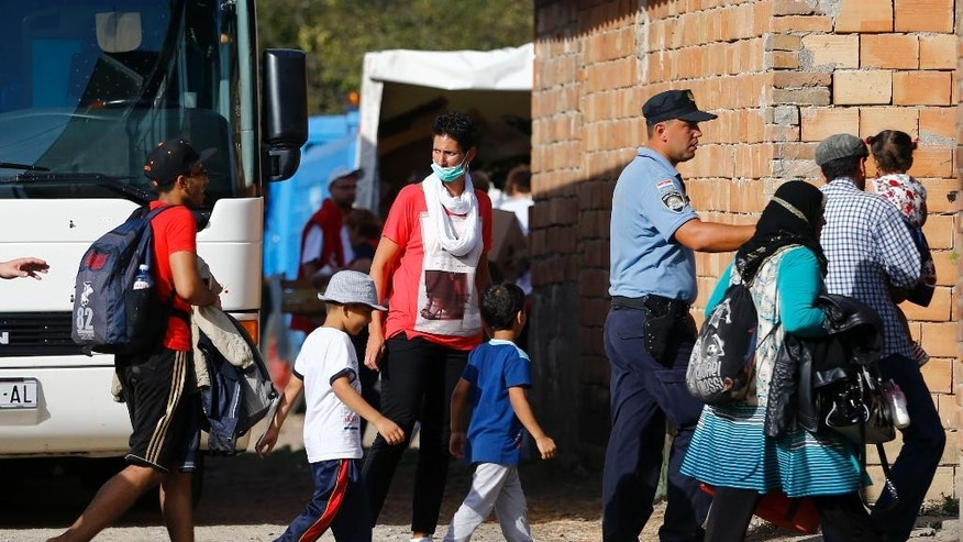 Migrants are guarded by a Croatian police officer on their way to the registration area after crossing the border line between Serbia and Croatia near Tovarnik, eastern Croatia, Wednesday, Sept. 16, 2015. First groups of migrants have started arriving in Croatia - a new entry point into the European Union after Hungary sealed off its border with Serbia with  coils of barbed wire. (AP Photo/Matthias Schrader)