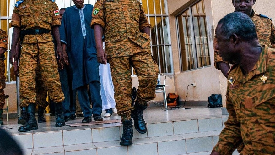 FILE - In this Nov. 4, 2014 file photo, Burkina Faso Prime Minister Lt. Col. Yacouba Isaac Zida , center, leaves a government building after meeting with political leaders in Ouagadougou, Burkina Faso.  Soldiers detained Burkina Faso's transitional president and prime minister Wednesday, Sept. 16, 2015,  raising fears of a coup just weeks before the country was to hold an election to replace its longtime leader who was ousted in a popular uprising late last year. (AP Photo/Theo Renaut,File)