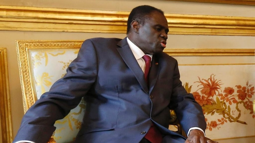 In this June 1,  2015 photo, Burkina Faso's transitional president Michel Kafando meets with French president Francois Hollande at the Elysee Palace in Paris, France. Soldiers arrested Burkina Faso's transitional president and prime minister Wednesday, Sept. 16, 2015, raising fears of a coup just weeks before the country was to hold an election to replace its longtime leader who was ousted in a popular uprising late last year. (Ian Langsdon/Pool Photo via AP)