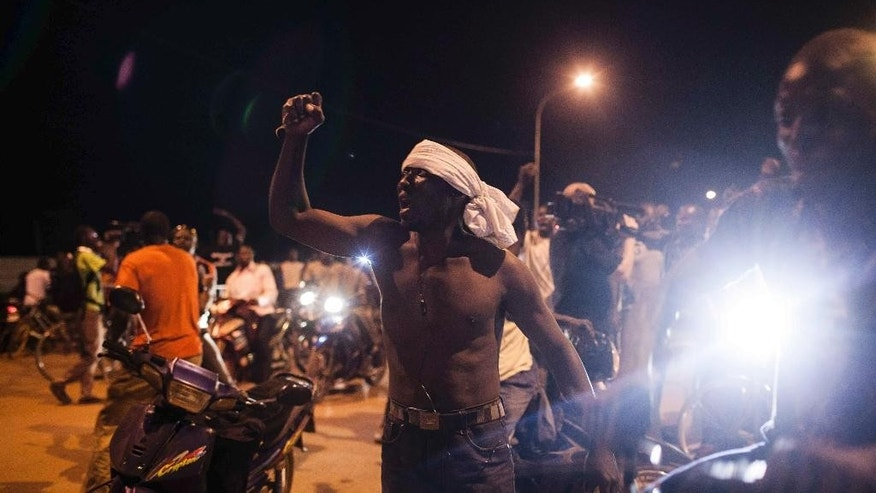 People demonstrate near the presidential palace after soldiers arrested Burkina Faso's transitional president and prime minister in Ouagadougou, Burkina Faso, Wednesday, Sept. 16, 2015. Soldiers arrested the two transitional leaders Wednesday, raising fears of a coup just weeks before the country was to hold an election to replace its longtime leader who was ousted in a popular uprising late last year. (AP Photo/Theo Renaut)