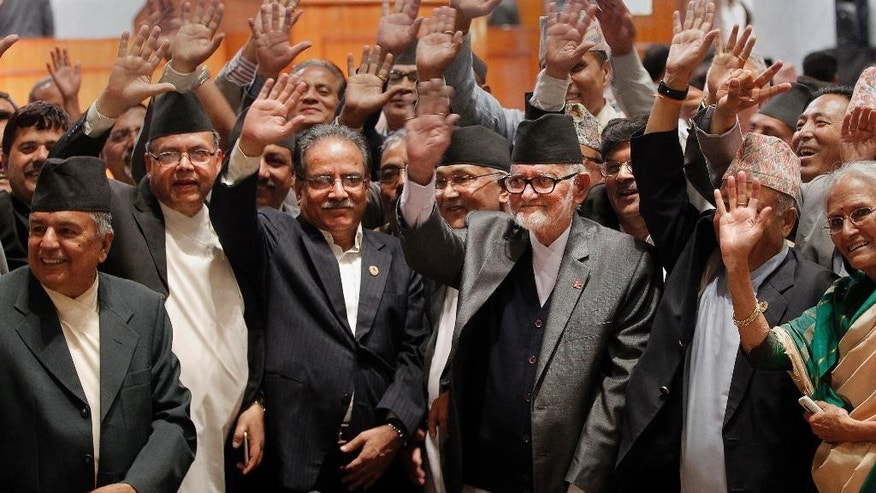 Nepal's Prime Minister Sushil Koirala, third right, and Communist Party of Nepal (Maoist) Chairman Pushpa Kamal Dahal, third left, along with others wave hands after the final constitution process at Constitution Assembly hall in Kathmandu, Nepal, Wednesday, Sept. 16, 2015. Nepal's Constituent Assembly has overwhelmingly approved a new constitution that has been delayed for years because of differences between political parties. (AP Photo/Niranjan Shrestha)
