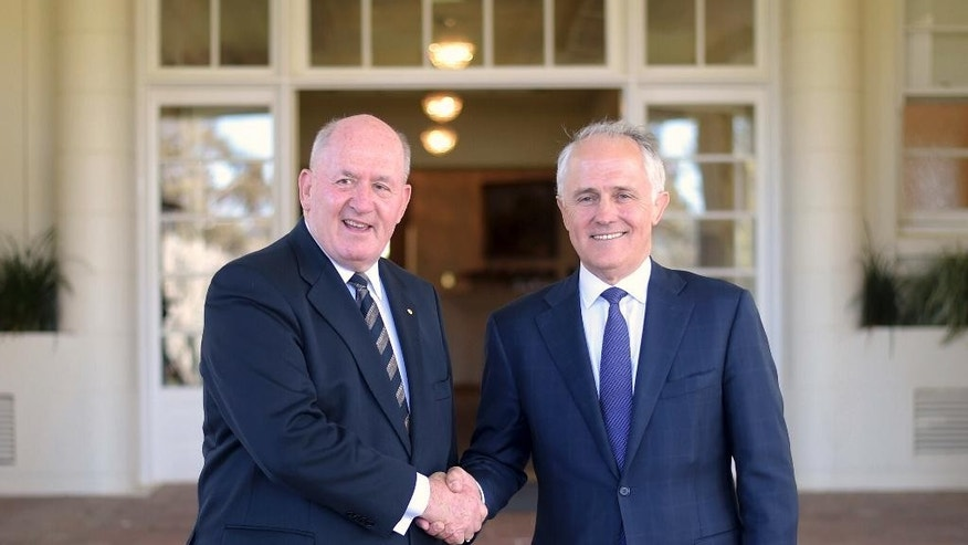 FILE - In this Tuesday, Sept. 15, 2015 file photo, Australian Prime Minister Malcolm Turnbull, right, shakes hands with Australia's Governor-General Sir Peter Cosgrove at Government House in Canberra after Turnbull was sworn in as Australia's 29th prime minister. The honeymoon did not last long for Turnbull. Just days after he took over as prime minister of Australia the attacks have started, with opponents accusing him of selling his ideological soul on issues from climate change to gay marriage in order to snatch the nation's top job. (Lukas Coch/Pool Photo via AP, File)