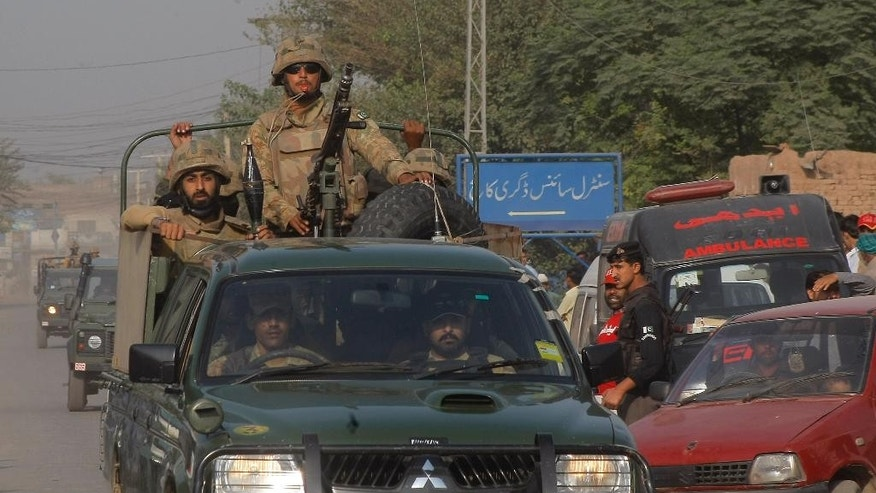 Pakistan army troops rush towards an air force base in Peshawar, Pakistan, Friday, Sept. 18, 2015. Militants in northwestern Pakistan attacked an air force base on the outskirts of Peshawar early Friday, triggering a shootout that left at least 20 wounded and six of the attackers dead, officials said. (AP Photo/Mohammad Sajjad)