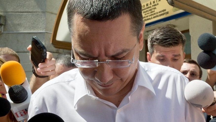 FILE - In this Monday, July 13, 2015 file photo, Romanian Premier Victor Ponta is surrounded by media as he exits the national anti-corruption prosecutors office where he was questioned in Bucharest, Romania. Romanian prosecutors on Thursday Sept. 17, 2015 formally indicted Prime Minister Victor Ponta on corruption charges, including tax evasion and money-laundering, and said he will be tried by the country's top court. (AP Photo/Vadim Ghirda, File)