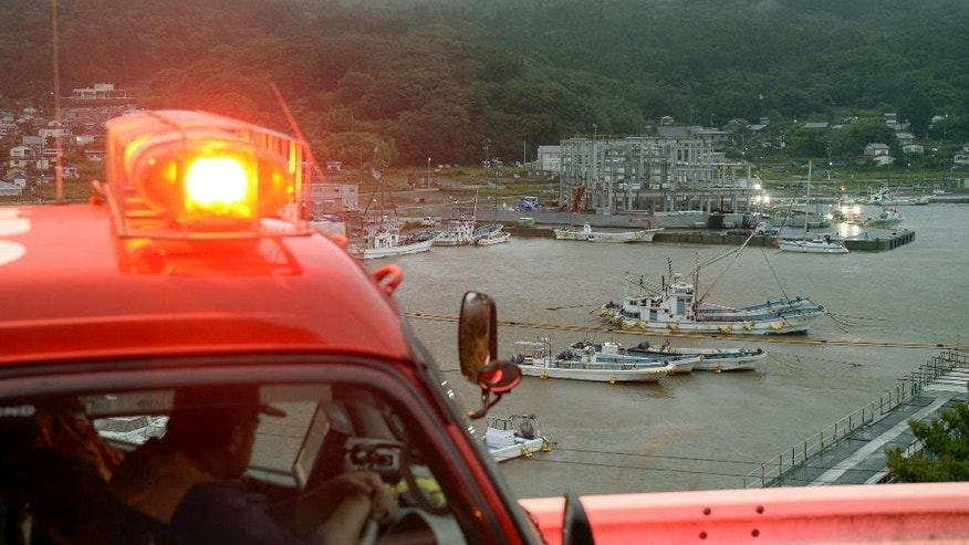 Firefighters keep eyes on Ayukawa Port in Ishinomaki, Miyagi prefecture, northeastern Japan after a tsunami advisory was issued before dawn for Japan's entire Pacific coast Friday, Sept. 18, 2015. Small tsunami waves reached the Japanese coast Friday morning, one day after a magnitude 8.3 earthquake struck offshore Chile. The Japan Meteorological Agency said a wave of 80 centimeters (31 inches) was recorded in the port of Kuji in Iwate prefecture, part of the same northeast region hit by a much larger and deadly tsunami in March 2011. (Yohei Kanasashi/Kyodo News via AP) JAPAN OUT, CREDIT MANDATORY