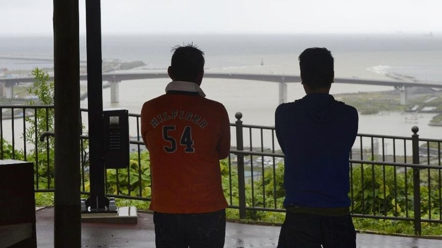 Two men watch the sea from the top of a hill in Ishinomaki, Miyagi prefecture, northeastern Japan after a tsunami advisory was issued for Japan's entire Pacific coast Friday, Sept. 18, 2015. Small tsunami waves reached the Japanese coast Friday morning, one day after a magnitude 8.3 earthquake struck offshore Chile. The Japan Meteorological Agency said a wave of 80 centimeters (31 inches) was recorded in the port of Kuji in Iwate prefecture, part of the same northeast region hit by a much larger and deadly tsunami in March 2011. (Yohei Kanasashi/Kyodo News via AP) JAPAN OUT, CREDIT MANDATORY