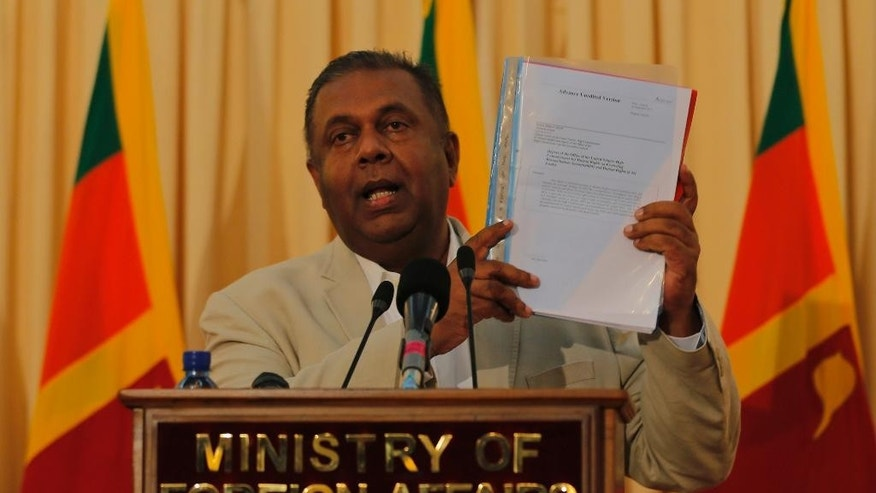 Sri Lankan Foreign Minister Mangala Samaraweera speaks holding a copy of the UN Human Rights Office report on Sri Lanka at a media briefing in Colombo, Sri Lanka, Thursday, Sept. 17, 2015. Samaraweera said Sri Lanka will begin talks next month on creating a special court to examine alleged atrocities during the country's civil war, in which tens of thousands of people died. (AP Photo/Eranga Jayawardena)