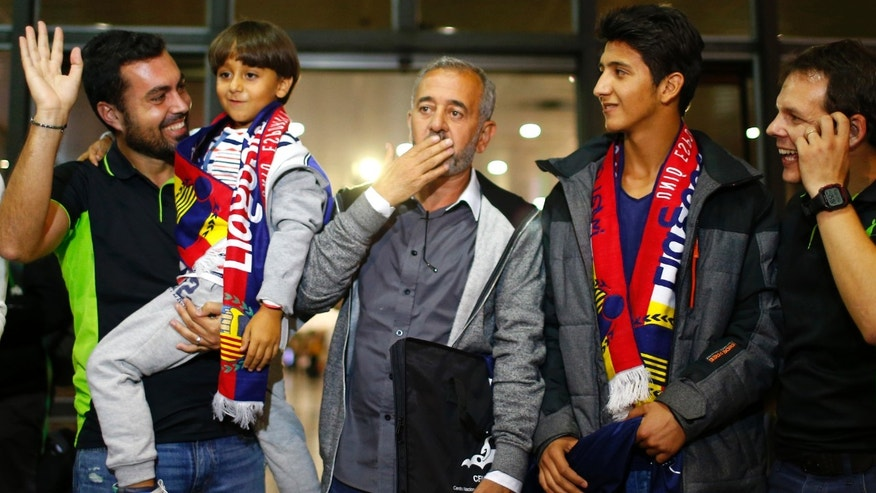 Syrian Osama Abdul Mohsen, center, reacts next to his son Zaid, left, as they arrive at the Barcelona train station on Wednesday, Sept.16, 2015. The Syrian refugee tripped at a border hotspot by a Hungarian journalist in an incident captured on video that generated global outrage will live in a Madrid suburb after a Spanish soccer academy convinced him to take an apartment offer and help to rebuild his life, an official with the school said Wednesday. Osama Abdul Mohsen was on a train expected to arrive in Madrid at midnight Wednesday. (AP Photo/Manu Fernandez)