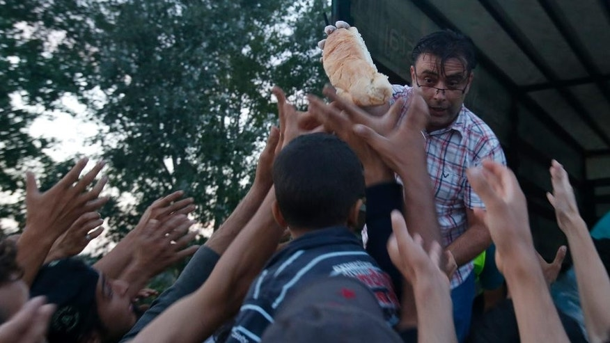 "Migrants reach for food being distributed, at the ""Horgos 2"" border crossing into the Hungary, near Horgos, Serbia, Wednesday, Sept. 16, 2015. Small groups of migrants continued to sneak into Hungary on Wednesday, a day after the country sealed its border with Serbia and began arresting people trying to breach the razor-wire barrier, while a group arrived in Croatia seeking another way into the European Union. (AP Photo/Darko Vojinovic)"