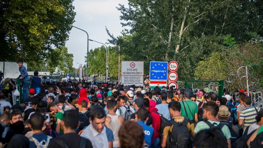 Migrants demonstrate at the border crossing into Hungary, near Horgos, Serbia, Wednesday, Sept. 16, 2015. The border crossing was closed by the Hungarian police after the Hungarian government declared a state of crisis due to mass migration, meaning special measures to fight illegal immigration, in two Hungarian counties bordering Serbia. (Tamas Soki/MTI via AP)