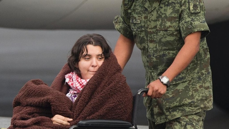 A Mexican woman wounded in an attack by the Egyptian army while traveling in Egypt, is transferred from her return flight to a waiting helicopter at the presidential hangar of Benito Juarez International Airport in Mexico City, Friday, Sept. 18, 2015. Eight other Mexicans died Sunday when Egyptian forces hunting militants mistakenly attacked their convoy in the western desert. Four other people died in the attack on the convoy, which was led by Egyptian guides. Their nationalities were not confirmed. (AP Photo/Rebecca Blackwell)