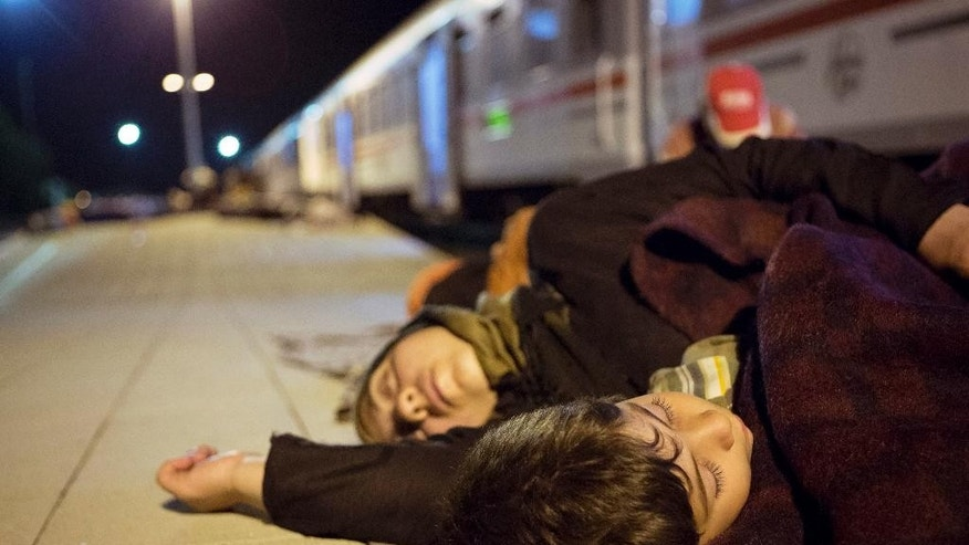 Migrants rest near a train at the railway station in Beli Manastir, near Hungarian border, northeast Croatia, early Friday, Sept. 18, 2015. Croatia has suddenly become the latest hotspot in the 1,000-mile plus exodus toward Western Europe after Hungary sealed off its border Tuesday with a razor-wire fence and then used tear gas, batons and water cannons to keep the migrants out. (AP Photo/Darko Bandic)