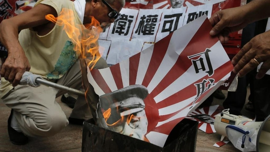 "An anti-Japan protester burns a Japanese military flag with a cutout picture of Imperial Japanese Army Gen. Hideki Tojo, an executed Class-A war criminal, during a rally near the Japanese Consulate General in Hong Kong, Friday, Sept. 18, 2015, to protest against Japan's ruling Liberal Democratic Party that pushed contentious security bills through a legislative committee. The Chinese words on the flag read: "" Shame ! "" (AP Photo/Vincent Yu)"