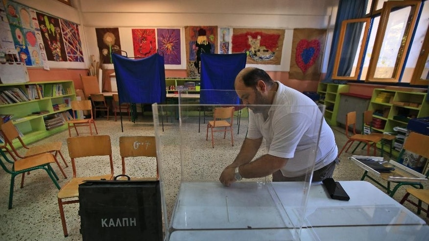 A municipal worker sets up a ballot box among other election materials at a school's classroom, in central Athens, Friday, Sept. 18, 2015, that will be a polling station for Sept. 20 elections. The box reads in Greek: 'Ballot box'. It is the third time this year Greeks will be voting, with the economy still in dire straits, a quarter of workers jobless, and capital controls limiting cash access to savings to 420 euros ($470) per week. (AP Photo/Lefteris Pitarakis)