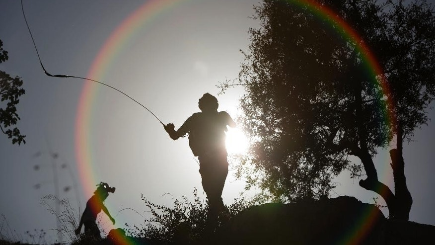 A Palestinian man uses a slingshot during clashes with Israeli troops outside Ofer military prison near the West Bank city of Ramallah, Thursday, Sept. 17, 2015. Palestinians in the West Bank protest in solidarity with protesters against the increasing number of Jewish visitors to the Al-Aqsa mosque compound in Jerusalem's Old City. (AP Photo/Majdi Mohammed)