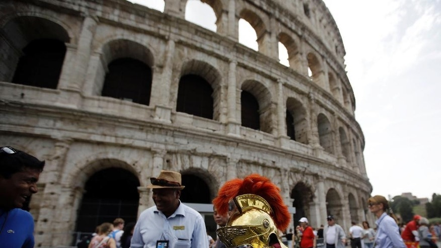 A reproduction of an ancient Roman centurion helmet is placed on a trash bin in front of the Colosseum, as notices inform visitors of the monument's temporary closure Friday morning due to an archaeological workers union meeting, in Rome, Friday, Sept. 18, 2015. (AP Photo/Gregorio Borgia)