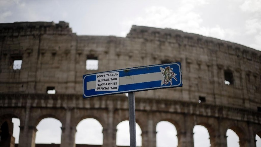 A note is attached on a street sign in front of the Colosseum, in Rome, Friday, Sept. 18, 2015. The monument temporary closed Friday morning due to an archaeological workers union meeting. (AP Photo/Gregorio Borgia)