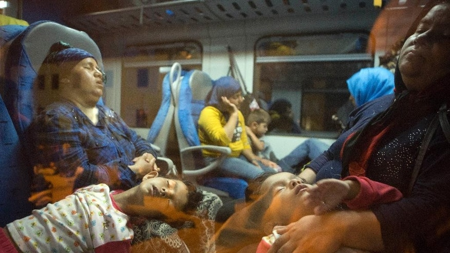 Migrants rest in a train at the railway station in Beli Manastir, near Hungarian border, northeast Croatia, early Friday, Sept. 18, 2015. Croatia has suddenly become the latest hotspot in the 1,000-mile plus exodus toward Western Europe after Hungary sealed off its border Tuesday with a razor-wire fence and then used tear gas, batons and water cannons to keep the migrants out. (AP Photo/Darko Bandic)