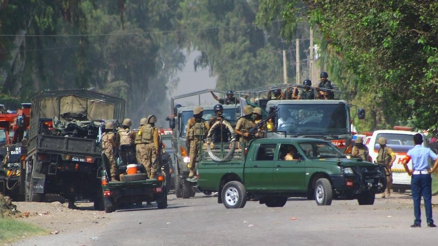 Pakistani army troops surround an air force base, Friday, Sept. 18, 2015 in Peshawar, Pakistan after the Taliban launched a brazen assault on the base on the outskirts of the northwestern city, storming a mosque inside the sprawling compound and killing many worshippers during prayers. (AP Photo/Mohammad Sajjad)