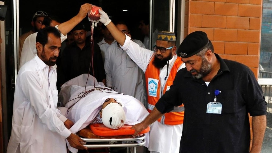 Pakistani volunteers carry an injured person to a local hospital, Friday, Sept. 18, 2015 in Peshawar, Pakistan after the Taliban launched a brazen assault on a military base on the outskirts of the northwestern city, storming a mosque inside the sprawling compound and killing many worshippers during prayers. (AP Photo/Mohammad Sajjad)
