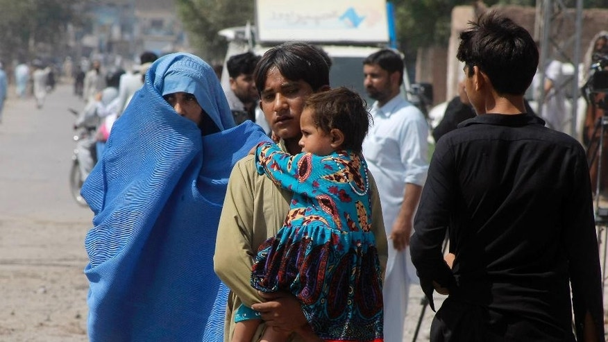 Residents leave the troubled area near an air force base where operation against the Taliban is in progress, Friday, Sept. 18, 2015 in Peshawar, Pakistan after the militants launched a brazen assault on a the base on the outskirts of the northwestern city, storming a mosque inside the sprawling compound and killing many worshippers during prayers. (AP Photo/Mohammad Sajjad)