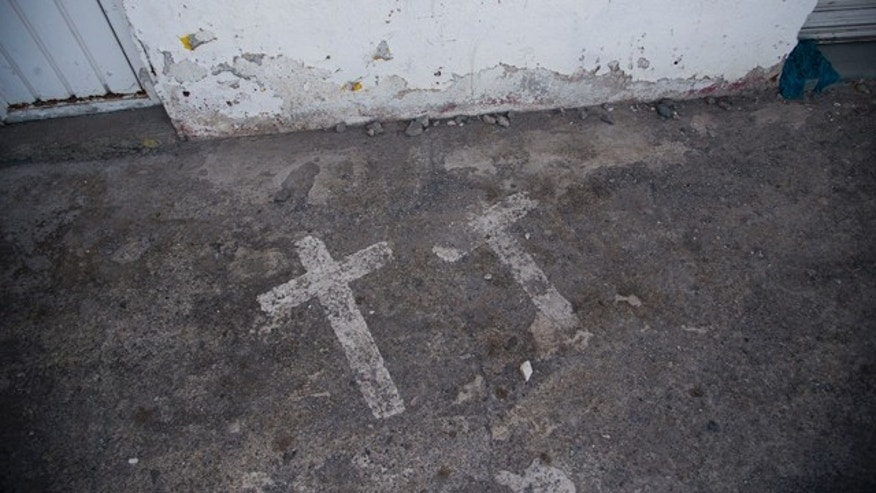 In this Aug. 19, 2015 photo, painted crosses mark the site where two college students were killed and 43 more kidnapped, in Iguala, Mexico on Sept. 26, 2014. According to a federal investigation, the students were taken by police and then handed over to a local drug gang that allegedly killed them and burned the bodies. (AP Photo/Dario Lopez-Mills)