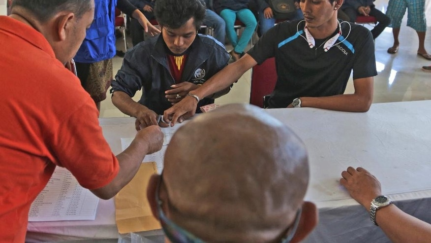 In this Tuesday, Sept. 8, 2015 photo, Burmese fisherman Kyaw Zayar, right, helps his friend Nge Nge, center, to translate a document Nge Nge has to sign in order to receive his unpaid salary in Ambon, Maluku province, Indonesia. Kyaw Zayar is among more than 2,000 fishermen rescued this year from forced labor under brutal conditions, mainly in remote Indonesian islands. The 30-year-old from Myawaddy, Myanmar, was forced to work on a fishing boat for nearly five years. (AP Photo/Achmad Ibrahim)