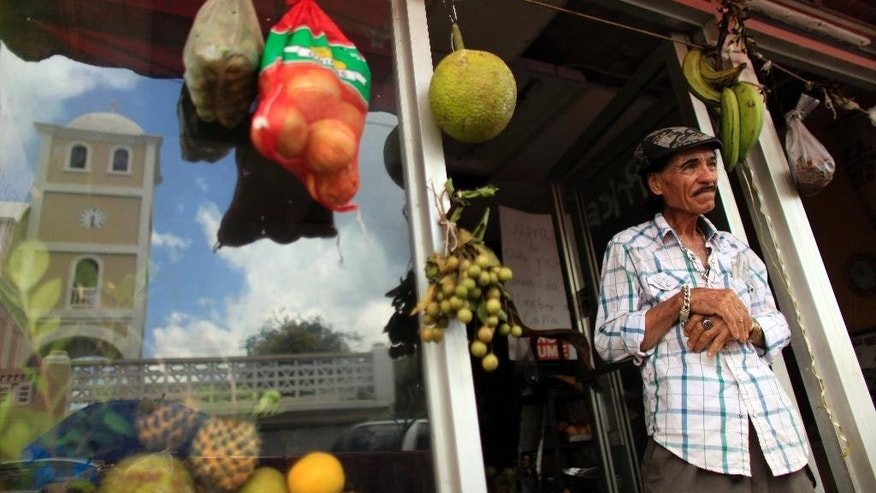 In this Sept. 2, 2015 photo, Angelo Lopez, 74, stands in front of his fresh fruit store in Lares, Puerto Rico. Lares has become emblematic of the economic stagnation that is overwhelming Puerto Rico, and those who live here believe the town is a warning sign of things to come across the island if the government doesn't emerge soon from its nearly decade-long financial slump. (AP Photo/Ricardo Arduengo)