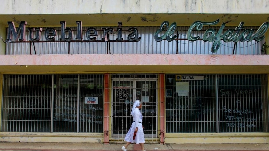 In this Sept. 2, 2015 photo, a nun walks in front of a closed down furniture store in Lares, Puerto Rico. The town of some 30,000 people has lost more residents than any other municipality in Puerto Rico in the last four years, and it has the island's second-highest unemployment rate at 22 percent.  (AP Photo/Ricardo Arduengo)