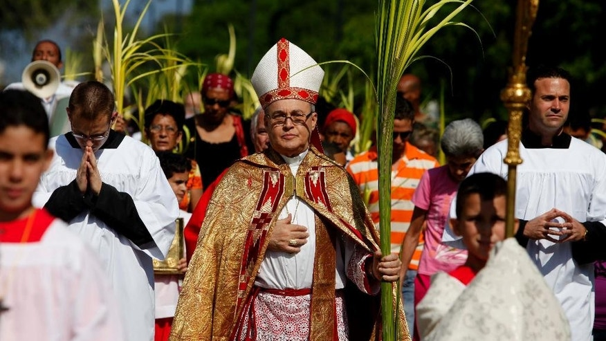 FILE - In this March 28, 2010, file photo, the Archbishop of Havana, Cardinal Jaime Ortega leads a procession of worshippers before Palm Sunday mass at the Cathedral in Havana.  Pope Francis has a close relationship with Cardinal Ortega, who has overseen the church's relationship with the Cuban state since 1981. Ortega has been fiercely criticized by dissidents in Cuba and anti-Castro forces in Miami for not confronting Raul Castro's government as the church has done in other places around the world. (AP Photo/Javier Galeano, File)