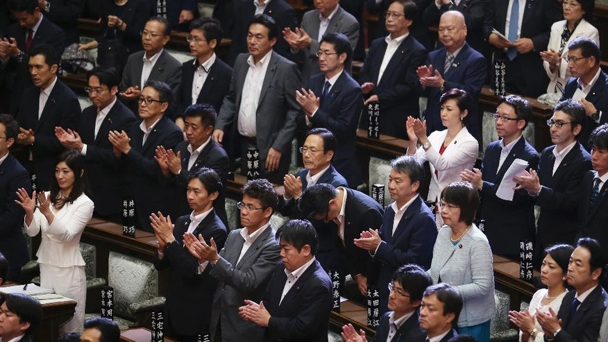 Japan's ruling party lawmakers and others who supported legislation loosening post-World War II constraints on the use of force by the military, applaud after the legislation was passed in a vote by the upper house, Tokyo, Saturday, Sept. 19, 2015. Japan's parliament approved contentious legislation to loosen constraints on the country's military, giving it a greater role. (AP Photo/Koji Sasahara)