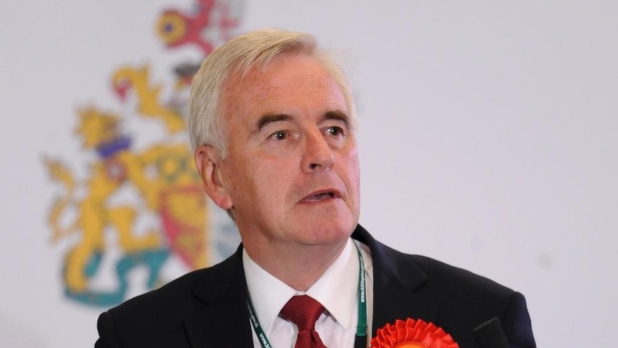 FILE - In this May 8, 2015 file photo MP John McDonnell speaks during a meeting in London.  A top official in Britain's Labour Party has apologized for saying Irish Republican Army bombings and shootings helped bring about peace in Northern Ireland. John McDonnell, a veteran left-wing lawmaker, was appointed Labour's Treasury spokesman this week by new party leader Jeremy Corbyn. (Andrew Matthews/PA File via AP)  UNITED KINGDOM OUT