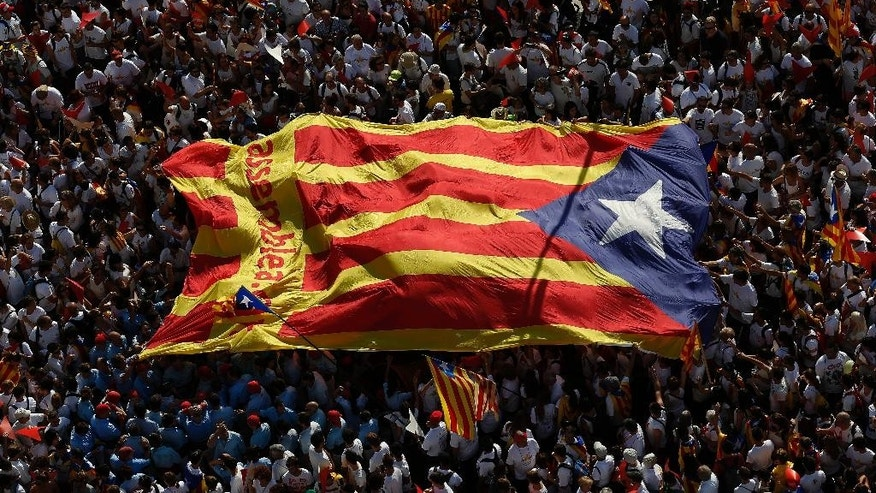 "FILE - In this Friday, Sept. 11, 2015 file photo, people carry a giant ""estelada"" flag, a symbol of Catalonian pro-independence, during a demonstration calling for the independence of Catalonia in Barcelona. Spain's main banking associations warned Friday that a victory for Catalonia's secession drive would create severe banking problems for the new Mediterranean nation left outside the European Union. (AP Photo/Manu Fernandez, File)"