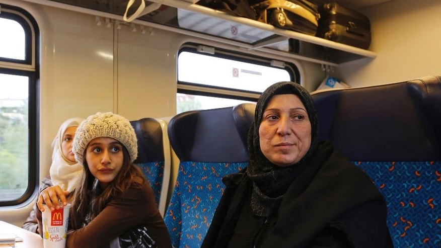 In this Sept. 16, 2015 photo Raghad Habashieh and her mother Khawla Kareem sit in a train in Berlin that brings them to Dresden from where they continued their journey to Chemnitz. On Tuesday afternoon, the family _44-year-old Khawla Kareem, her daughters Reem, 19, and Raghad, 11, and sons Mohammed, 17, and Yaman, 15 _ finally got their papers, all stamped, with passport photos, a new address and train tickets to go to Chemnitz, a city of 240,000 near the Czech border. (AP Photo/Ferdinand Ostrop)