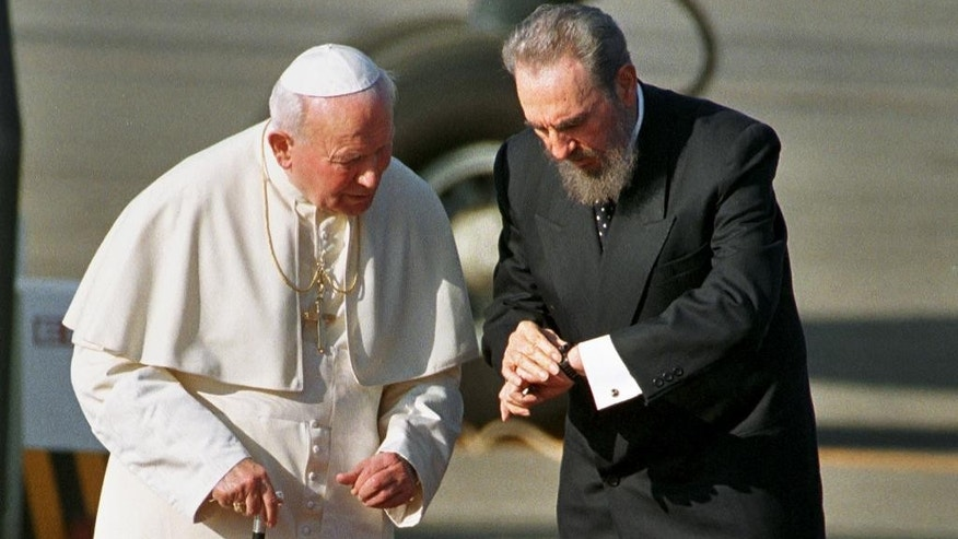 FILE - In this Jan. 21, 1998 file photo, Cuba's President Fidel Castro, and Pope John Paul II check the time during a welcoming ceremony in Havana, Cuba. Havana workers were given the afternoon off, on a sunny 80-degree day. Tens of thousands of Cubans, organized by neighborhood and workplace, lined the 12-mile route from the airport. Some sang hymns and waved tiny yellow and white Vatican flags and the red, white and blue Cuban banner. The Cuban president himself, a diehard Marxist-Leninist, urged people to turn out for the island's first papal visit ever. (AP Photo/Jose Goitia, File)